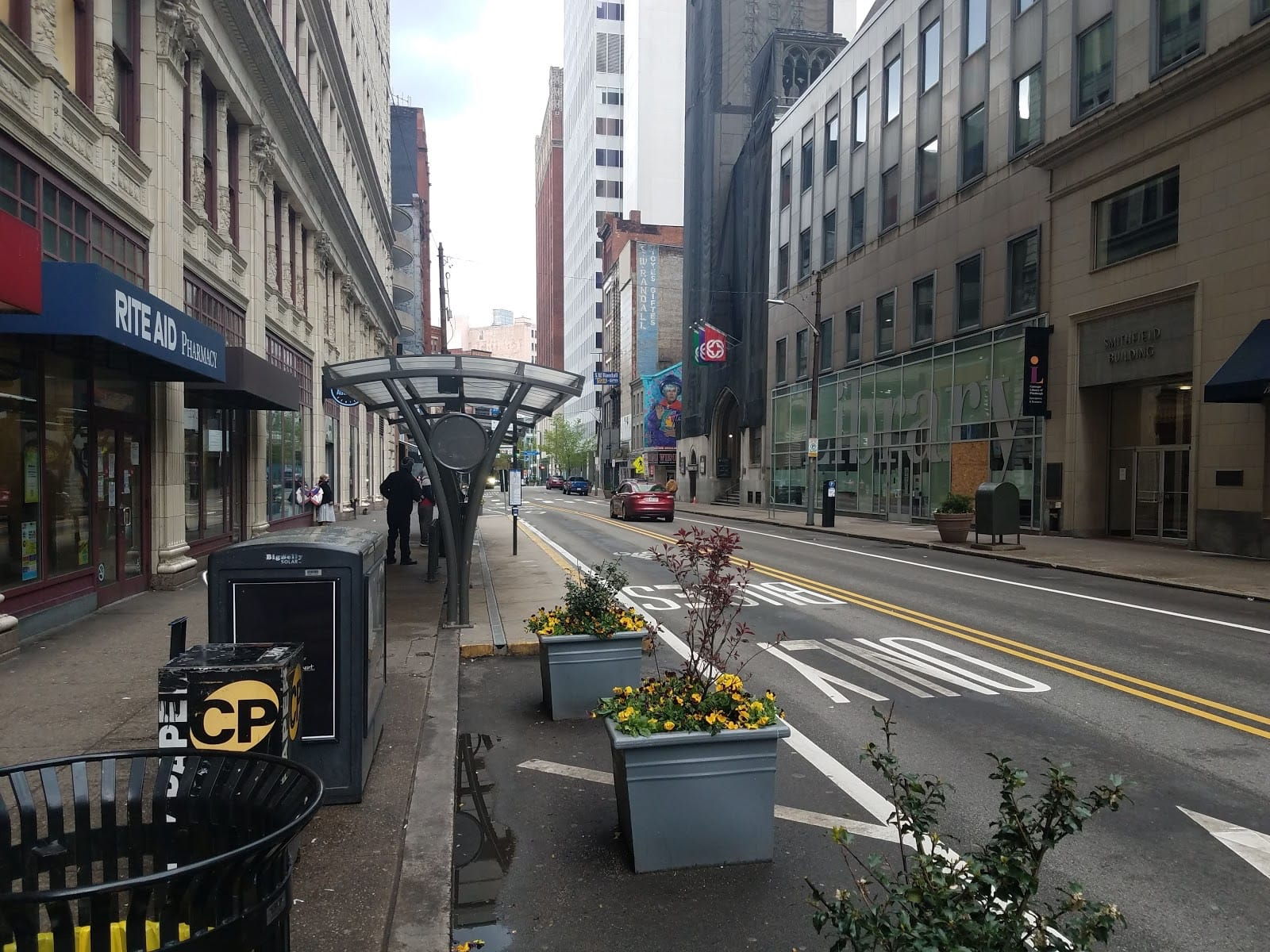 On Smithfield St in Downtown, an extended curb allows for the installation of a bus shelter for waiting passengers and planters, as well as freeing up the sidewalk for pedestrians.