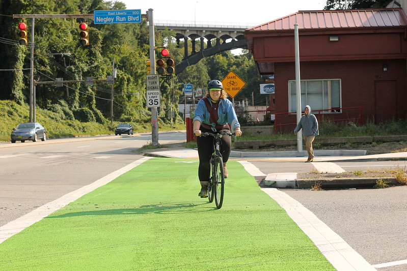 A person on a bicycle rides in the new green painted path on Washington Blvd at Negley Run